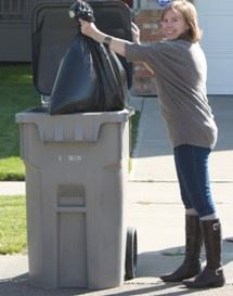 Woman throwing away bagged waste